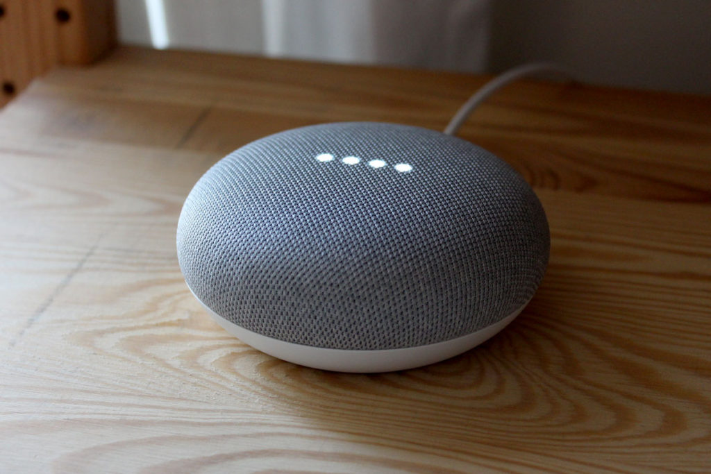 A Google Home Mini smart speaker responding to a request